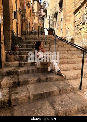 Frau sitzt auf Schritte, Valetta, Malta - Stockfoto