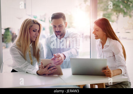 Drei junge lächelnd fröhlichen Kollegen zusammenarbeiten auf laptop - Stockfoto
