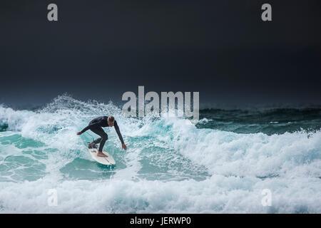 Surfen Großbritannien. Ein einsamer Surfer auf einer Welle als dunkle Wolken über der Küste von North Cornwall. - Stockfoto
