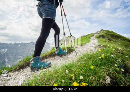 Frau läuft auf schmalen Bergweg mit Wanderstöcken. - Stockfoto