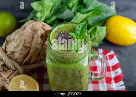 Gesundes Grün Spinat Smoothie in einem Glas Becher verziert mit Minze und Chia Samen mit Zutaten auf der karierten - Stockfoto