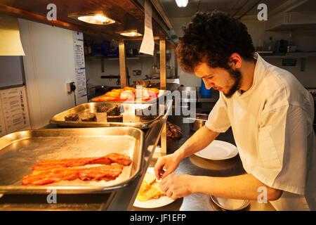 Koch in einer Restaurantküche bei einem Zähler Beschichtung Essen, Tabletts mit Speck, Blutwurst und gegrillten - Stockfoto