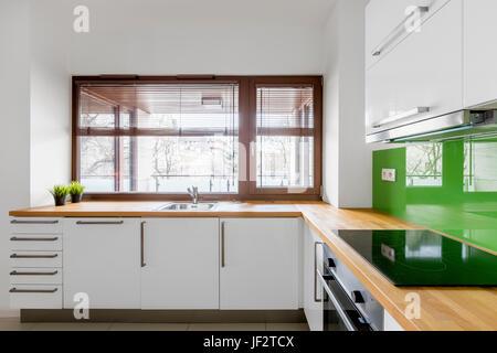 Weiße Küche Mit Modernen Schränke, Grüne Backsplash Und Fenster   Stockfoto