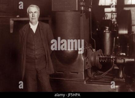 Alva (1847 – 1931), US-amerikanischer Erfinder und Unternehmer, stehend mit seinem ursprünglichen Dynamo bei Edison Works in Orange, New Jersey, c1906.