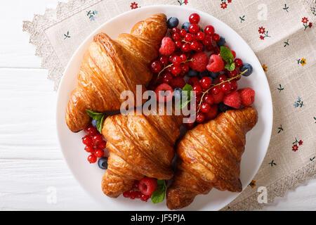 Leckeres Buttercroissant mit frischen Beeren hautnah auf einem Teller. horizontale Ansicht von oben - Stockfoto