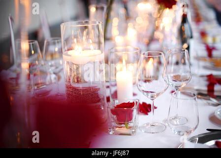 Romantisches Candle-light Dinner Tischdekoration mit eleganten Glaswaren und rote Blüten über einer weißen Tischdecke - Stockfoto