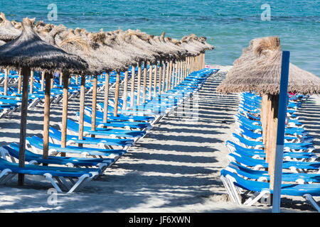 Liegestühle und Sonnenschirme in einer Reihe - Stockfoto