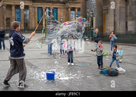Ein Straßenmusikant entstehen Bläschen für Kinder auf The Mound, Edinburgh, Schottland, Vereinigtes Königreich. - Stockfoto
