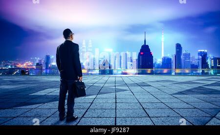 Geschäftsmann, schauen und denken Sie Dach mit modernen Stadt Skyline Hintergrund, Nachtaufnahme. - Stockfoto