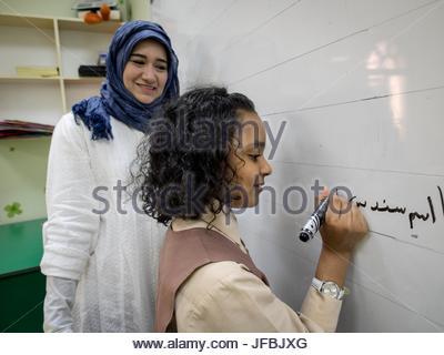 Ein Lehrer-Uhren ein 10 Jahres altes Mädchen auf einem Brett zu schreiben. - Stockfoto