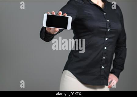 Business-Frau präsentieren eine mobile Anwendung oder ein Foto. Mädchen halten Smartphone mit dynamischen Pose und - Stockfoto