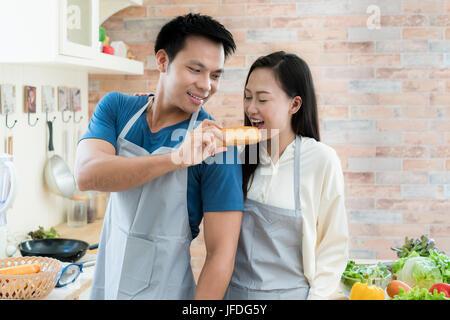 Asiatischen schöne junge Paar füttert Brot Lächeln beim Kochen in der Küche zu Hause. Glückliche Liebespaar im Haus. - Stockfoto