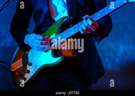 Nahaufnahme von einem Musiker spielen auf der E-Gitarre bei einem Konzert