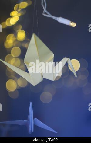 Papier-gelbem Kranich-Origami auf einem dunklen Hintergrund Weihnachtsgirlande. - Stockfoto
