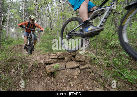 Mountainbiker, die Durchführung von Stunt im Wald - Stockfoto