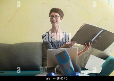 Frau mit gebrochenem Bein von zu Hause aus arbeiten - Stockfoto