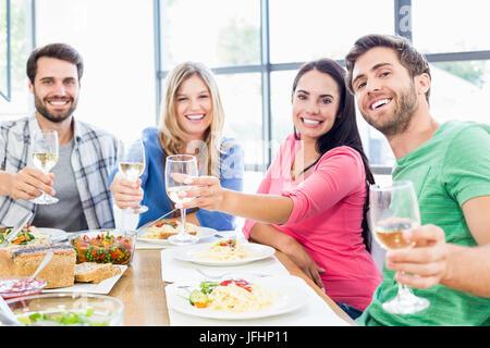 Freunde, toasten Gläser Wein während einer Mahlzeit - Stockfoto