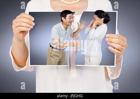 Zusammengesetztes Bild der Frau, die ein zerrissenes Foto - Stockfoto