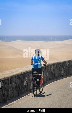 Rückansicht des Frau Radfahren auf Straße von Düne und Meer - Stockfoto