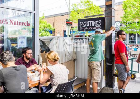 Montreal, Kanada - 28. Mai 2017: Jean Talon Market Poutine Restaurant Zeichen in Gebäude mit Personen an Tischen - Stockfoto