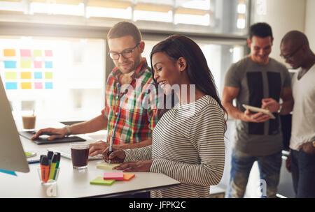 Junge Frau die Notizen mit Kollegen beim Menschen Surfen die Tablette im Büro. - Stockfoto