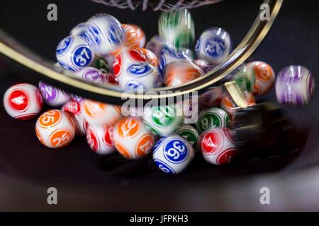 Bunte Lotto-Kugeln in eine Bingo-Maschine. Lotto-Kugeln in eine Kugel in Bewegung. Spielautomaten und Zubehör. Verschwommene - Stockfoto
