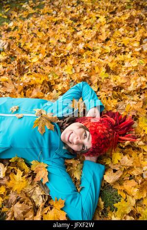 Lächelnde Frau in Haufen von Herbst am Boden liegen lässt - Stockfoto