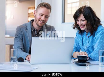 Zwei lächelnde junge Mitarbeiter, die mit einem Laptop in einem Büro - Stockfoto