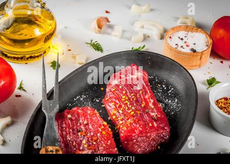 Fleisch, Rindfleisch. Frische rohe Steaks in einer Pfanne erhitzen. Gewürze (Salz, Pfeffer), frisches Gemüse - Tomaten, - Stockfoto