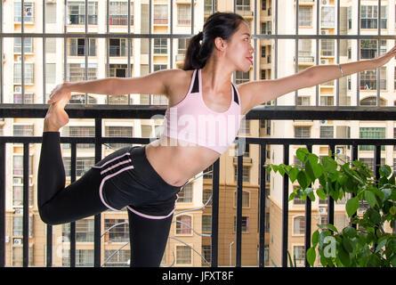 Mädchen tun stehenden Bogen Yoga Pose Variation auf dem Balkon - Stockfoto