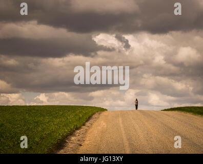 Junges Mädchen am Horizont Fuß leer Bauernhof Straße mit Kulturen auf beiden Seiten. Bewölkten Tag. - Stockfoto
