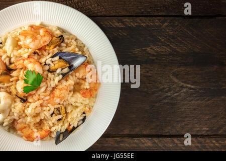 Meeresfrüchte Risotto auf dunklen rustikalen Hintergrund mit Exemplar - Stockfoto