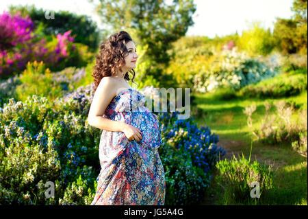 Ziemlich schwanger Frau posiert in einem grünen Rosmarin-Garten - Stockfoto
