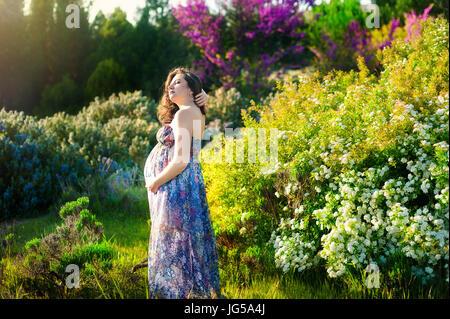 Schöne beeindruckende schwangere Frau in erstaunliche Sommerkleid. Konzept der Schwangerschaft, Gesundheit, Familie - Stockfoto
