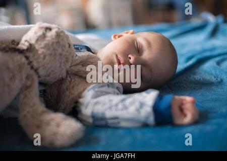 Niedliche Babyjungen schlafen mit Teddybär - Stockfoto