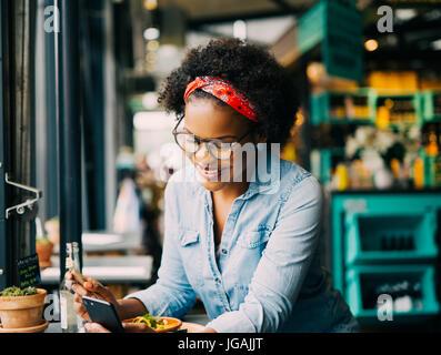 Lächelnde junge Afrikanerin Lesetexte auf ein Handy beim Sitzen allein an einem Schalter in einem Café genießen - Stockfoto