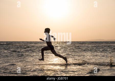 Junge läuft mit Freude auf dem Wasser. - Stockfoto