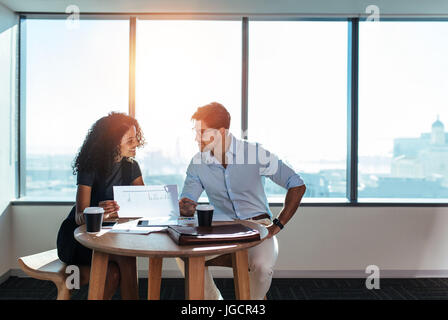 Junger Mann und Frau diskutieren arbeiten bei einer Tasse Kaffee im Büro zu sitzen. Geschäftsfrau hält eine Papier - Stockfoto