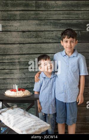 Zwei lächelnden jungen stehen neben einer Geburtstagstorte - Stockfoto