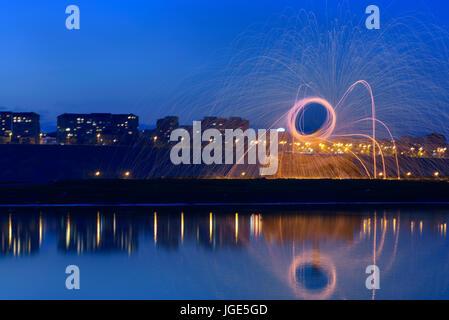 Heiße goldene Funken von man Spinnen brennen Stahlwolle in der Nähe des Flusses mit Wasser Reflexion. Fotos mit - Stockfoto