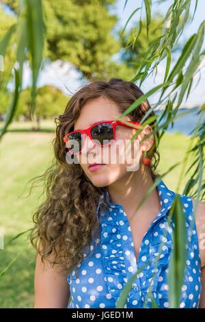 Porträt der jungen Frau in roten Sonnenbrillen stehen unter Weide im Sommer - Stockfoto