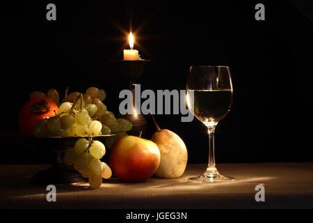 Vintage Stilleben mit Früchten in Schüssel geben und in der Nähe von Beleuchtung Kerze Weinglas - Stockfoto