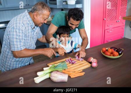 Lächelnder Mann sah junge schneiden Zwiebel mit Vater in der Küche zu Hause - Stockfoto