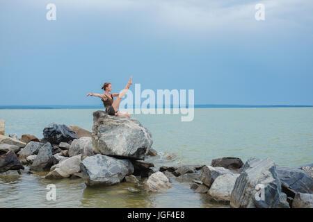 Mädchen üben von Yoga auf den Felsen gegen den blauen Himmel und das azurblaue Meer. Entspannung und Dehnung. Yoga - Stockfoto