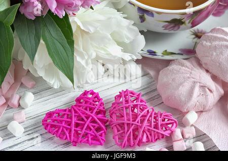 Päonien Blüten rosa Tasse Tee rattan Herzen Marshmallow auf weißem Hintergrund Holz-stock Bild - Stockfoto