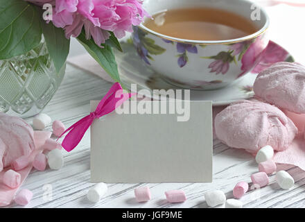 Päonien Blüten rosa Tasse Tee Grußkarte Marshmallow auf weißem Hintergrund Holz-stock Bild - Stockfoto