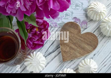 Päonien Blüten rosa Glas Tee mit braunem Holz- Herzen Marshmallow auf weißem Hintergrund Holz-stock Bild - Stockfoto