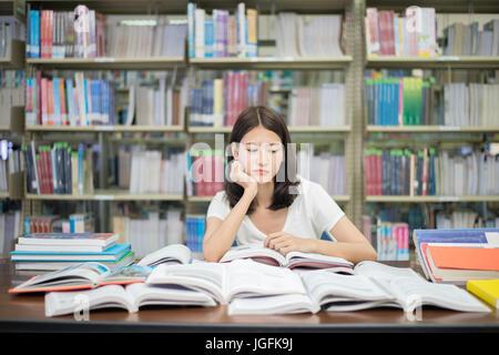 Asiatische Studentin langweilig Lesebuch in Bibliothek mit vielen Büchern in der Universität. Asiatische Studentin - Stockfoto