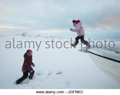 Mädchen im Teenageralter springen von einem Boot einen Angelausflug Familie arktischen Kabeljau mit Eis Löcher im - Stockfoto
