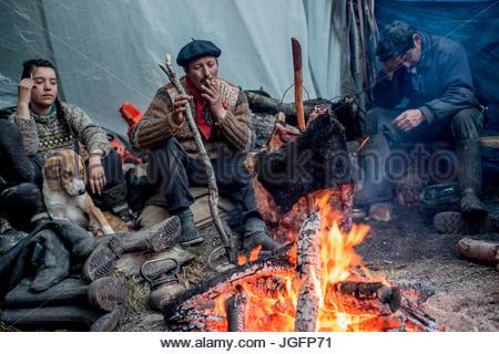Bagualeros, oder Cowboys, die wilden Tiere zu erfassen, kochen Fleisch am Spieß aus einem wilden Stier. - Stockfoto